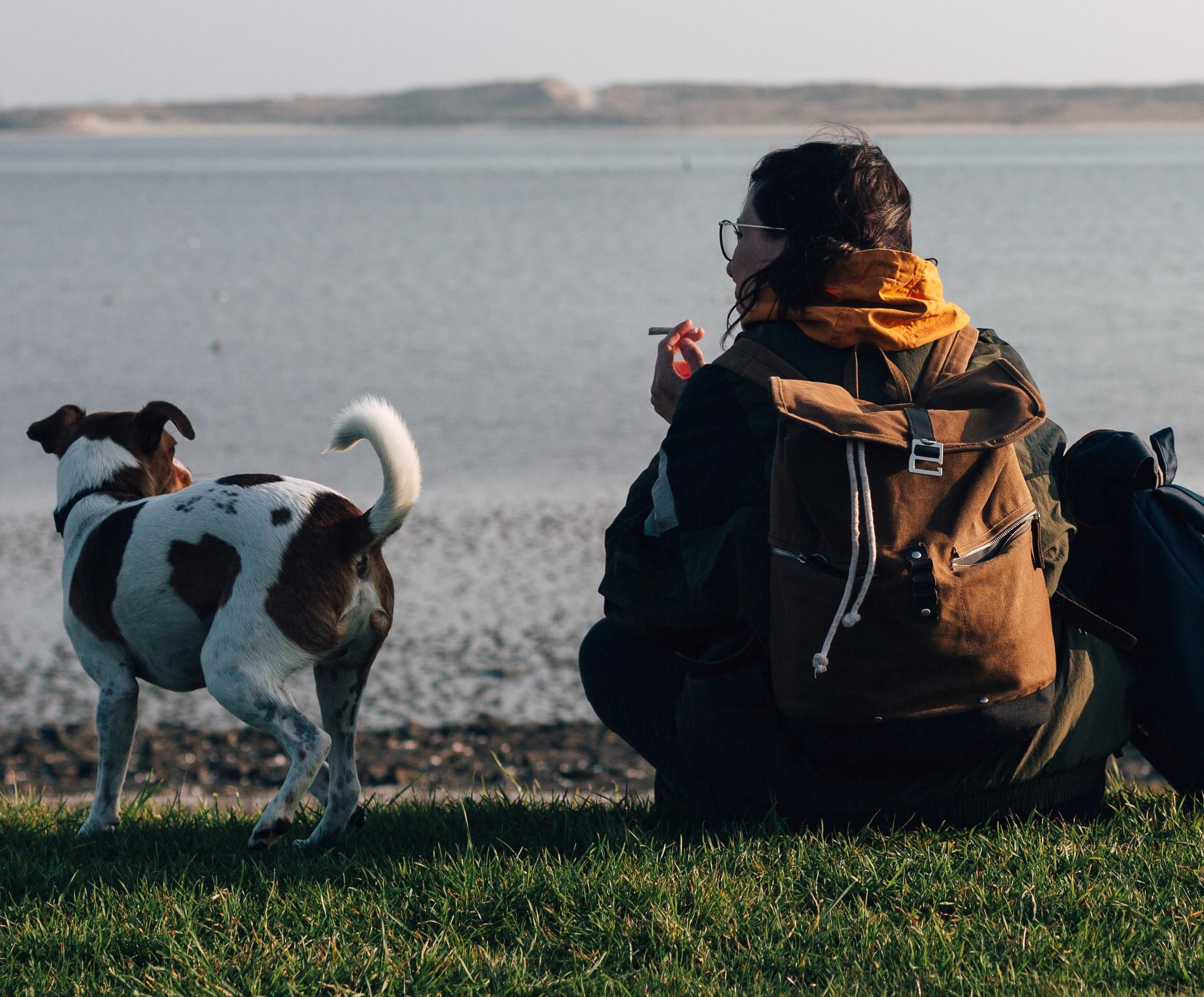 Woman on beach smoking by dog