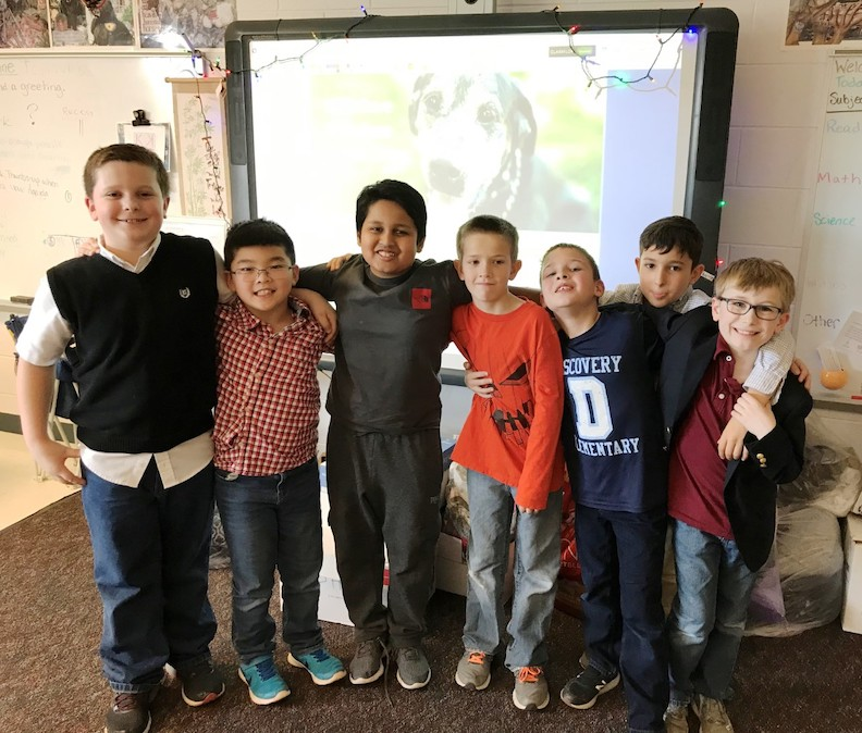 Seven third grade boys standing arm and arm