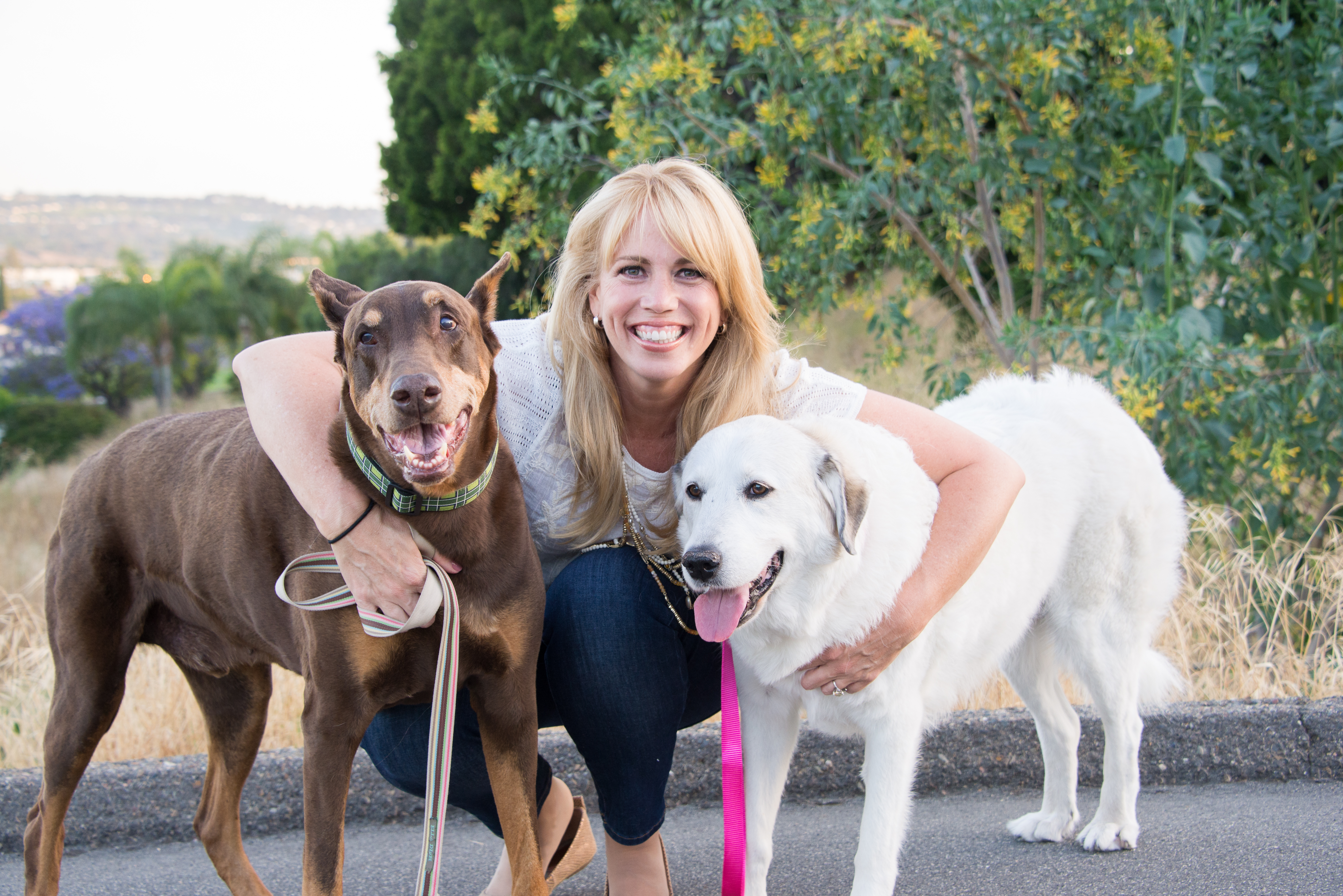 blonde woman between two large dogs