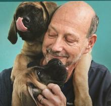 smiling man with 2 brown puppies