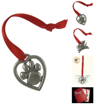 Ornament made of pewter in the shape of a heart with a paw inside