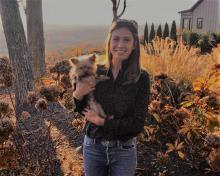 Woman in black long sleeve collar shirt & jeans holding yorkie dog. Standing on dirt with autumn colors and plants.