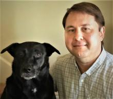 Man with short brown hair and button up sitting sitting with older black lab in front of a tan wall